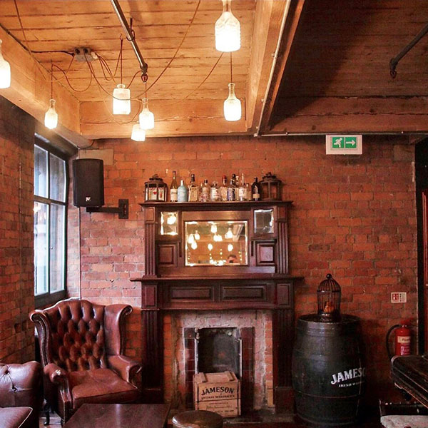The inside of Whiskey Jar showing an original fireplace and leather chair.